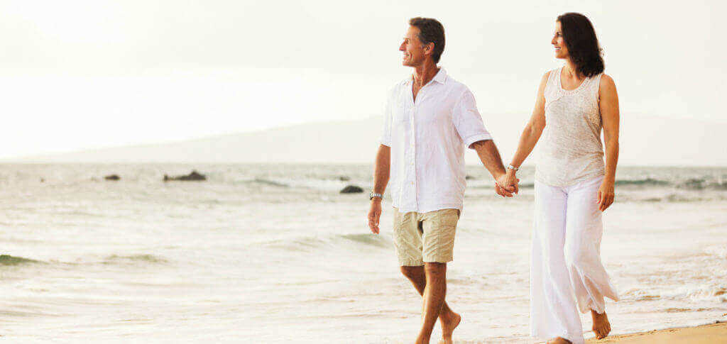A man and woman walking on a beach, looking content and peaceful.